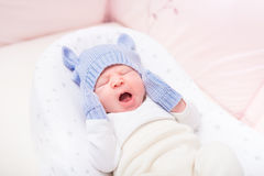Yawning little baby wearing knitted blue hat with ears. And mittens lying in beautiful cradle. Security and childcare concept royalty free stock photos