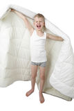 Yawning little boy stands going to wrap in blanket royalty free stock photography