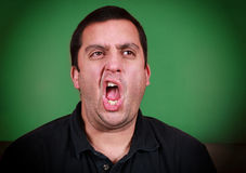 Yawning Man. A man who appears to be yawning or belching with a green background Royalty Free Stock Image