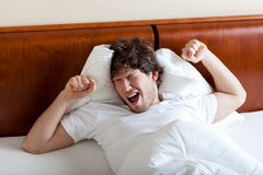 Yawning man after awakening. Young yawning man after awakening in bed Royalty Free Stock Photos