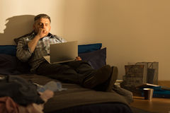 Yawning man on bed Stock Photography