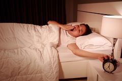 Yawning man being awakened by an alarm clock in his bedroom in m Royalty Free Stock Images