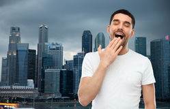 Yawning man over evening singapore city background. Rest, bedtime and people concept - tired yawning man over evening singapore city background Stock Photography