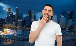 Yawning man over gray background. Travel, tourism, bedtime and people concept - tired yawning man over night singapore city background Royalty Free Stock Photos
