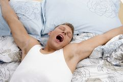 Yawning man stretching his arms stock photo