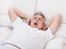 Yawning Mature Man Stretching His Arm Royalty Free Stock Images