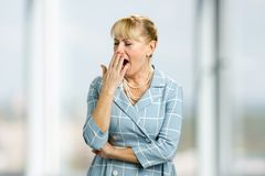 Yawning mature woman, blurred background. Royalty Free Stock Images