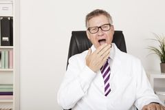 Yawning middle-aged male doctor Royalty Free Stock Photo