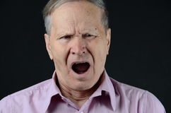 Yawning. Old man yawning with wide open mouth Royalty Free Stock Images