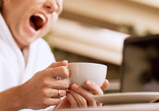 Yawning sleepy man with cup of coffee in hand Royalty Free Stock Image