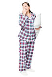 Yawning sleepy woman in warm pajamas holds ready pillow on white Stock Image