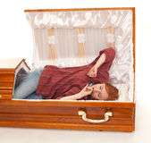 Yawning and stretching woman in the coffin Stock Photo