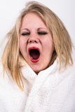 Yawning very tired young woman. With tousled hair and a bathrobe Stock Photography