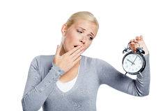 Yawning woman with alarm clock Royalty Free Stock Images