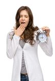 Yawning woman keeping alarm clock Royalty Free Stock Photo