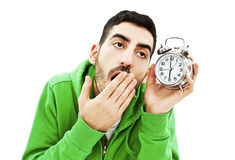 Yawning young man holding alarm clock Stock Photo