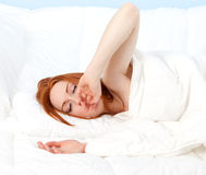 Yawning young woman in white bedding Royalty Free Stock Images