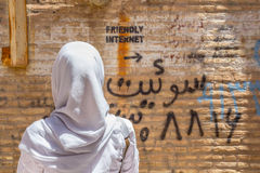 YAZD, IRÃ - 18 DE AGOSTO DE 2016: Mulher encoberta que olha uma inscrição na parede que indica o ponto sem cortes do Internet Foto de Stock Royalty Free