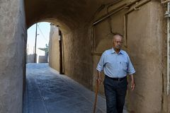 Old man passes under the arched vault, Yazd, Iran. stock photography