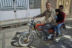 Family of three Iranians is riding motorbike on city street. Stock Image
