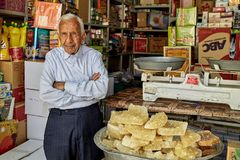 An elderly Iranian grocer stands at entrance to food store. Royalty Free Stock Photo