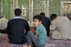 Male child is boring during muslim prayer, Yazd, Iran. Yazd, Iran - April 21, 2017: Shrine of Prince Fazel, The boy of primary school age is bored in the prayer royalty free stock photos