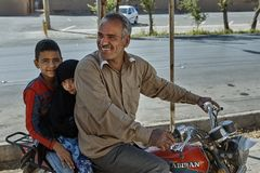 Children ride a motorcycle with their father, Yazd, Iran. Yazd, Iran - April 21, 2017:  A smiling mature Iranian rides a motorcycle with young children, a boy Royalty Free Stock Photography