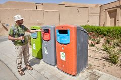 Traveler used recycling containers for glass, paper and plastic,. Yazd, Iran - April 22, 2017: The tourist used coloured recycling wheelie bins for sorting waste Stock Image