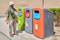 Tourist used coloured recycling wheelie bins for sorting waste,. Yazd, Iran - April 22, 2017: Traveler used recycling containers for glass, paper and plastic royalty free stock image