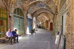 Two men sitting on cart in arched passage oriental bazaar. Yazd, Iran - April 22, 2017: Two men are sitting on a trolley in the vaulted passage of the eastern Royalty Free Stock Images