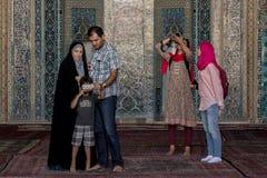 YAZD, IRAN - AUGUSTUS 18, 2016: Iraanse familie die een beeld op een smartphone bekijken terwijl de buitenlandse toeristen een be Stock Afbeelding