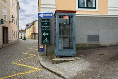 Telephone booth in the historical center of the town. Ybbs an der Donau, Austria. YBBS AN DER DONAU, AUSTRIA - JULY 8, 2018. Telephone booth on a paved street royalty free stock image