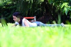 YBeautiful ung student som använder bärbara datorn på gräs Arkivfoton