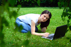 YBeautiful young student using laptop on grass. Photo of the Beautiful young student using laptop on grass Stock Image