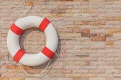 Życia boja wiesza na ściana z cegieł tle w pobliżu pływanie Fotografia Royalty Free