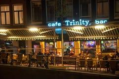 Życie nocne w czerwone światło okręgu, turyści cieszy się napoje w lokalnej kawiarni w Amsterdam holandie Zdjęcia Stock