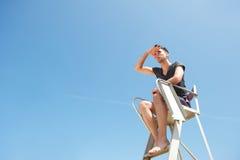 Życie strażnika obsiadanie w krześle patrzeje w odległość Fotografia Stock