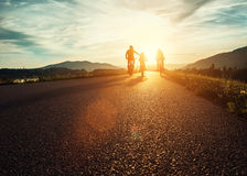 Сyclists family traveling on the road at sunset Stock Images