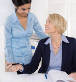 Życzliwa atmosfera przy pracą: dwa uśmiechnięty bizneswoman obraz stock