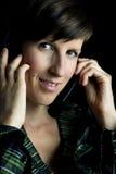 Życzliwa kobieta używa słuchawki z hełmofonami Fotografia Royalty Free
