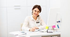 Życzliwa kobieta za recepcyjnego biurka administratorem obraz stock