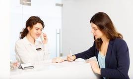 Życzliwa kobieta za recepcyjnego biurka administratorem z klientem zdjęcie royalty free