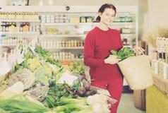 Życzliwa młoda kobieta wybiera sezonowych warzywa w rolnym sklepie zdjęcia stock