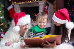 Życzliwa rodzinna czytelnicza książka na Bożenarodzeniowym wieczór Zdjęcia Royalty Free