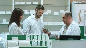 Życzliwa starsza farmaceuta daje salalry dolarowi jego yunger koledzy Fotografia Stock