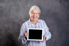Życzliwa szara kosmata starsza kobieta pokazuje pastylka komputer osobistego Fotografia Stock