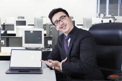Życzliwy biznesmen z pustym laptopu ekranem Fotografia Stock