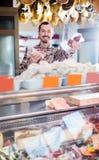 Życzliwy męski sklepowy asystent demonstruje rodzaje mięso w sklepie Fotografia Royalty Free
