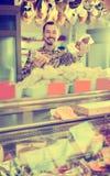 Życzliwy męski sklepowy asystent demonstruje rodzaje mięso w sklepie Zdjęcie Royalty Free