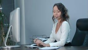 Życzliwy młody azjatykci żeński operator pracuje na laptopie z słuchawki przy nowożytnym biurem Obrazy Stock